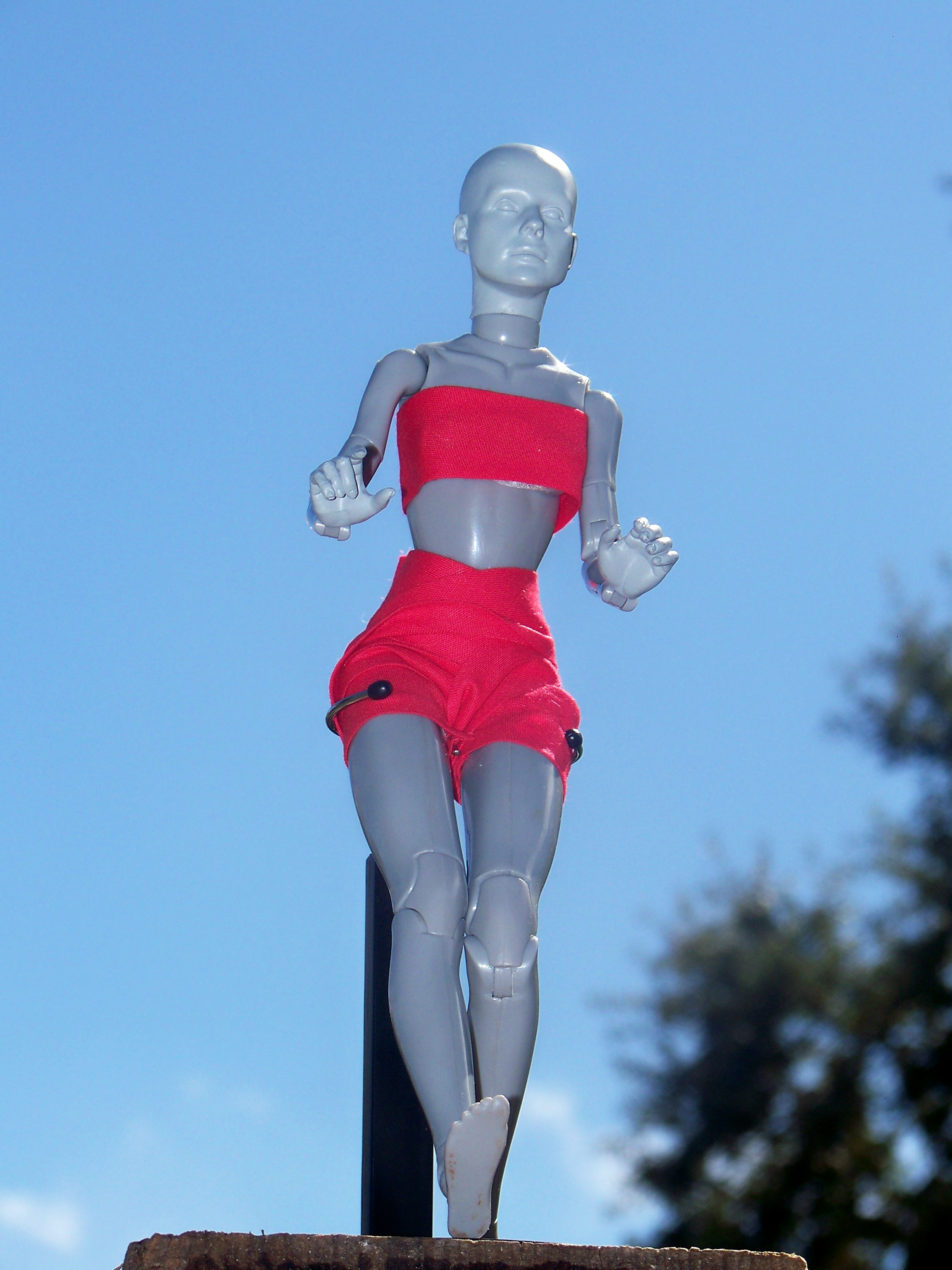 Plastic artist model demonstrating heel brake stance