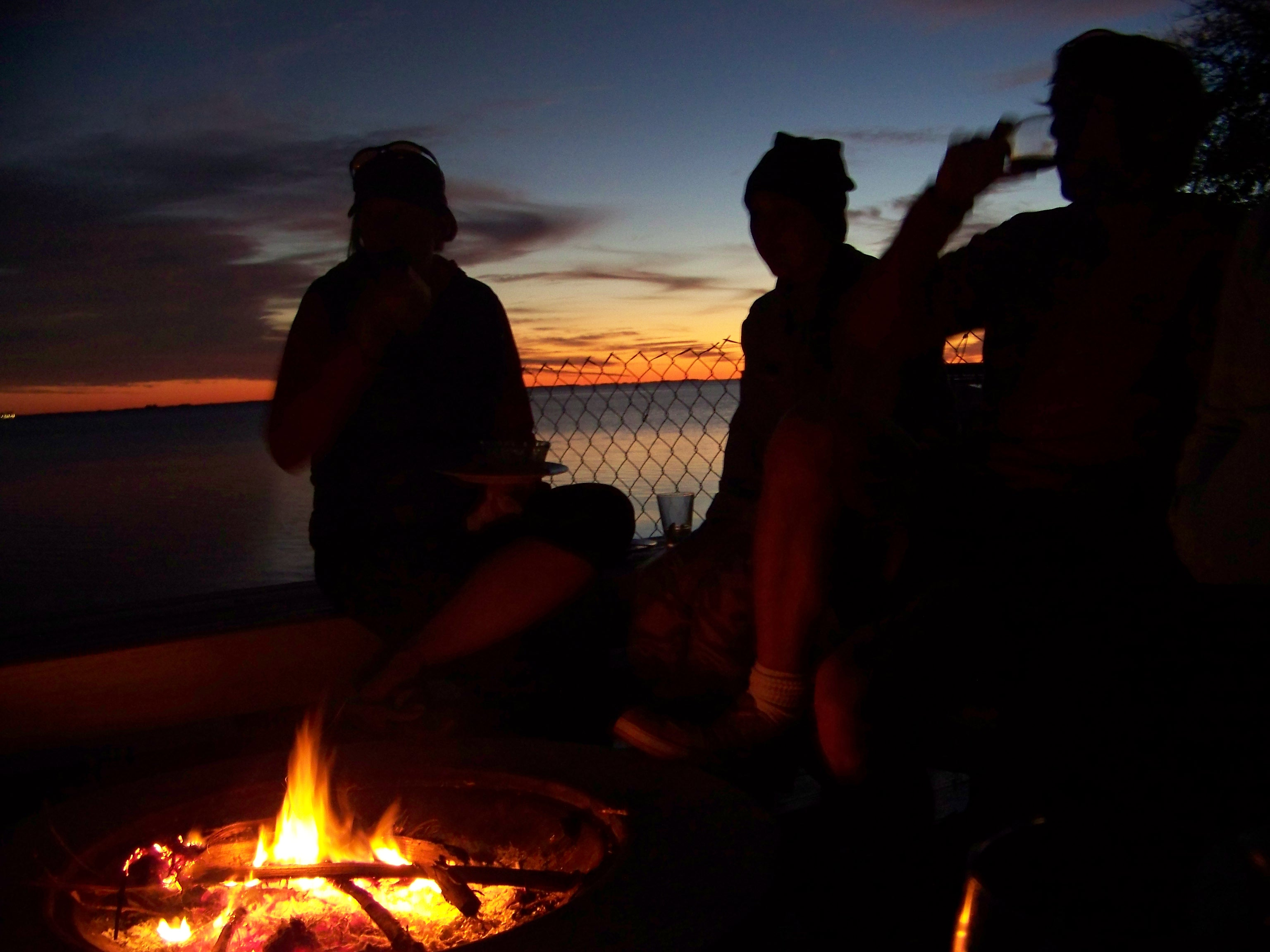 Party at sunset, silhouettes around the ca===pfire